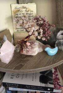 a setting of rose quartz and ceramic bird with a hadndmade wire and rose quartz tree in center