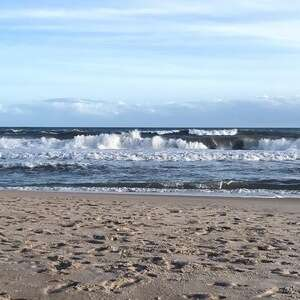 Rolling ocean waves under blue sky with smattering clouds