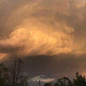 golden billowy clouds tiny rainbow after a storm